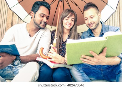 Multiracial students reading books outdoors holding umbrella - Portrait of multiethnic friends studying together sitting outside school - Soft vintage filter look with main focus on left male