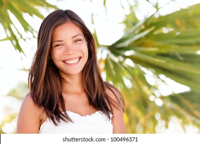 Multiracial summer woman portrait. Ethnic mixed Asian / Caucasian woman smiling happy on beach tanned and fresh looking at camera joyful. Youthful girl in her 20s.