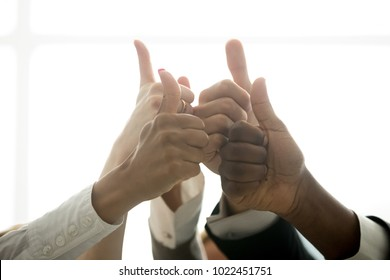 Multiracial team hands showing thumbs up finger gesture, motivated diverse corporate group showing like celebrating racial equality, successful teamwork, recommending business solution, close up view
