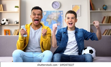 Multiracial teen boys rejoicing football team victory, watching match at home