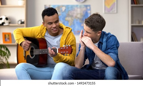 Multiracial teenage friends playing guitar and mouthorgan hobby musician career