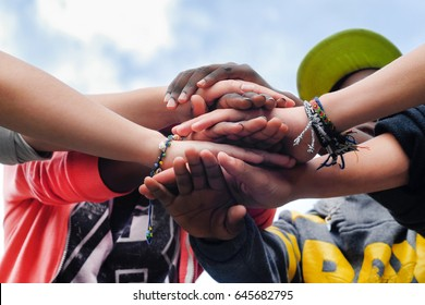 Multiracial teenagers joining hands together in cooperation