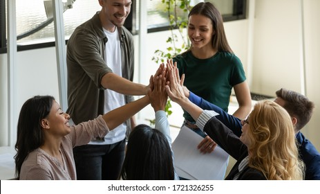 Multiracial workers with female leader, coach giving high five at company meeting, female teacher with students celebrating achievement, corporate success of teamwork, team building activity.