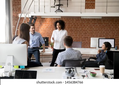 Multiracial young colleagues brainstorm in coworking space, talk discussing business ideas together, diverse millennial employees speak during informal briefing in modern office. Cooperation concept