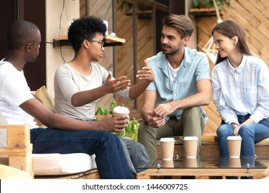 Multiracial young couples sit in coffeeshop drinking coffee talking sharing ideas relaxing together, multiethnic millennial friends have fun enjoying time in café chatting and communicating