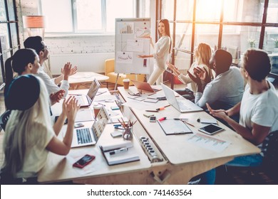 Multiracial young creative people in modern office. Group of young business people are working together with laptop, tablet, smart phone, notebook. Successful hipster team in coworking. Freelancers.