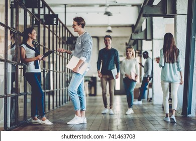 Multiracial young creative people in modern office. Group of young business people are working together. Successful hipster team in coworking. Freelancers walking in corridor.