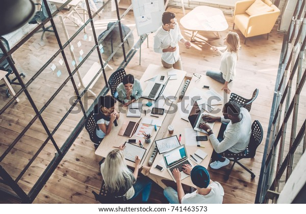 Multirassische junge kreative Menschen im modernen Büro. Gruppen junger Geschäftsleute arbeiten mit Laptop, Tablet, Smartphone, Notebook. Erfolgreiches Hipster-Team bei der Mitarbeit. Freiberufler