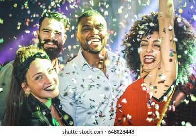 Multiracial young friends dancing at night club under confetti rain - Happy people having crazy fun at nightclub after party - Nightlife drunk concept with guys and girls celebrate at concert festival