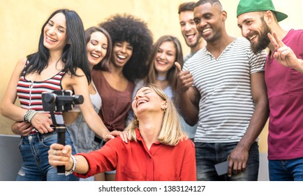 Multiracial young friends taking selfie with mobile smart phone and stabilizer gimbal - Friendship concept with millenial people having fun together sharing live feeds on social media networks