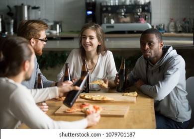 Multiracial young friends talking drinking beer eating pizza together, diverse millennial people sharing pub cafe pizzeria table, smiling students chatting having fun hanging out in public place