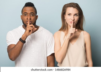 Multiracial young man and woman stand isolated on blue studio background make hush gesture, african American man and Caucasian woman look at camera tell secret, announce great sale offer