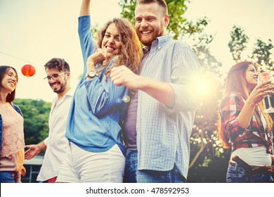 Multiracial young people dancing in backyard  - Cheerful multi ethnic friends drinking outdoor - New music entertainment trends