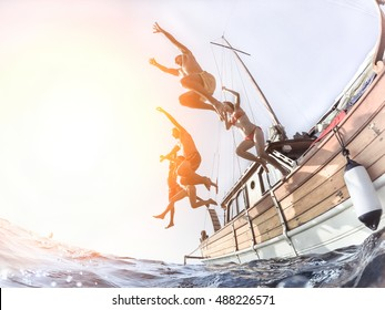 Multiracial young people diving from sailing boat into the sea - Cheerful friends having fun in summer party day - Vacation and friendship concept - Fisheye lens distortion with back lighting