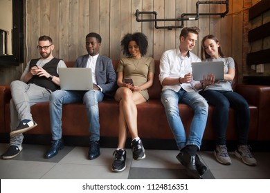 Multiracial young people obsessed with smartphones and laptops, sitting in row not talking to each other, diverse millennials addicted to different gadgets spending time together checking social media