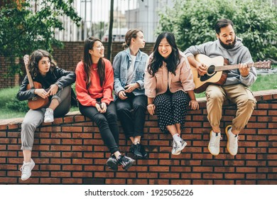 Multiracial young people playing guitar and singing on street.
