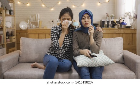 Multiracial young people watching sad movie in TV relax on sofa with home kitchen in background in bright cozy apartment. two asian chinese and muslim women friends upset crying using napkin tissue