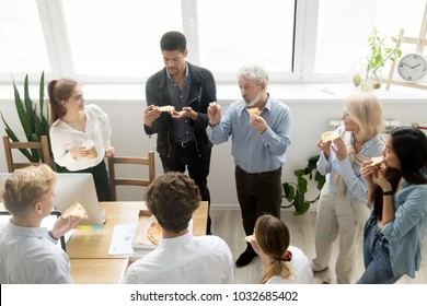Multiracial young and senior colleagues eating pizza and talking at corporate lunch in coworking office, friendly diverse project team staff people enjoying meal at break discussing new ideas together