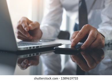 Multitasking business man working on laptop computer, touching, zooming in smart mobile phone screen and reflection on office desk with copy space, close up, business and financial concept