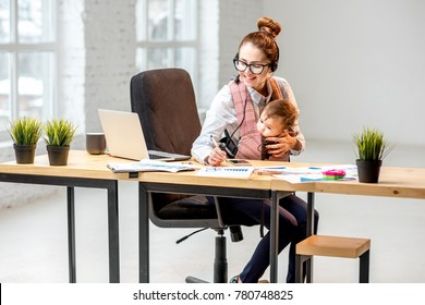 Multitasking businesswoman working with headset and laptop sitting with her baby son at the white office interior