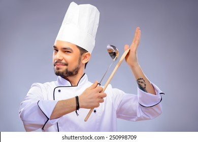 Multitasking is a chefs game. Closeup portrait of handsome cook holding a wooden culinary spoon and soup ladle and winking to camera while standing over grey background with copy space