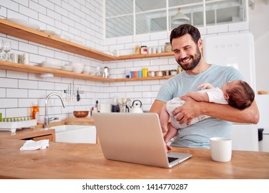 Multi-Tasking Father Holds Sleeping Baby Son And Works On Laptop Computer In Kitchen