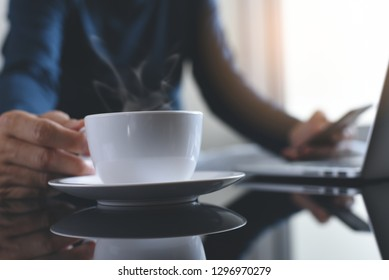 Multitasking man, freelance using mobile smart phone while working on laptop computer and drinking coffee at home with reflection on office desk, online business, social network communication concept