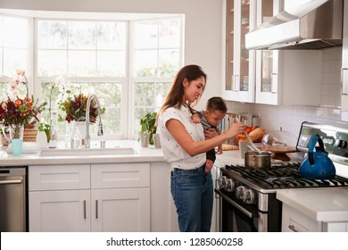 Multitasking mum holding her young baby while she makes food at the hob in her kitchen, side view