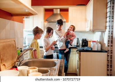 Multitasking mum is tending to all of her children at once in the kitchen of their home. She is feeding the baby a bottle while talking to her eldest children and looking at their smart phone.