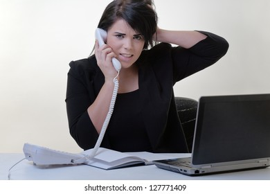 multitasking woman sitting at her desk trying to get through the day