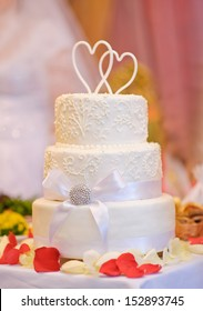 Multi-tiered white wedding cake with two hearts above
