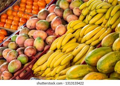 A multitude of colored fruits at the farmers' market - papaya, bananas, mango, kaki and kiwi