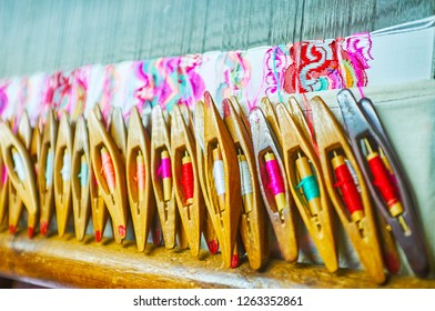 Multitude of wooden weaving flying shuttles for the handloom with colorful silk weft threads on pirns (rods), details of the pattern on produced fabric are seen on the background, Mandalay, Myanmar.