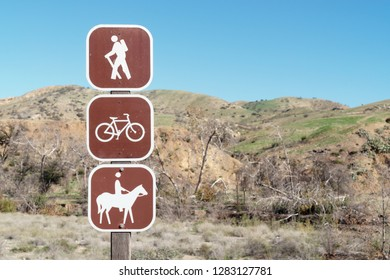 Multiuse trail sign on wood post. Brown and white hiking, biking, and horse riding icons. Blue sky and blurred hills in background. Room for text.
