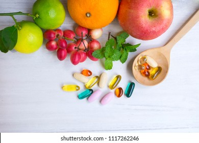Multivitamin supplements from fruit on white wooden background.Top view.