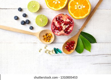 Multivitamin supplements on wooden spoon with healthy fruit blueberry, lime, orange, pomegranete on white wooden background.Top view.