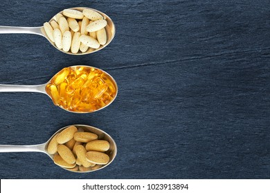 Multivitamins, fish oil and antioxidants on tablespoons