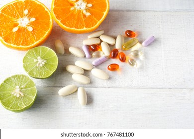 Multivitamins and supplements with fresh orange and lamon on white wooden background.