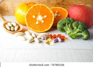 Multivitamins and supplements in wooden spoon with fresh fruits on white wooden background.