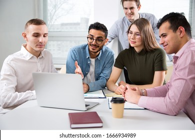 Multy-ethnic group of creative business people sitting at the office desk and working with computer