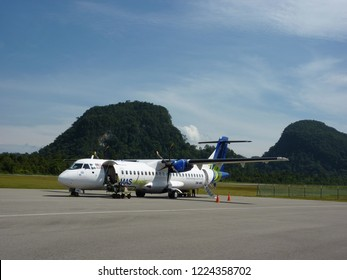 Mulu Airport, Borneo, Malaysia - August 24, 2009 : MASWings ATR 72-500 airplane stopped on the runway with a view of Mulu National Park in the background