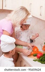 Mum with children prepares for vegetable salad on kitchen