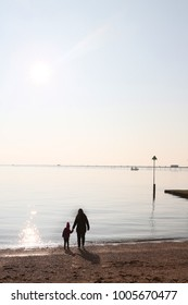 mum and daughter holding hands and looking out tohte view at southend beach, with the pier in the background on a calm winters day.