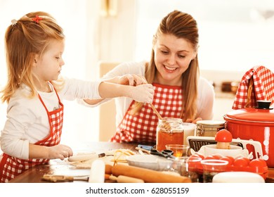 Mum and daughter spending time together making dough. Selective focus on girl's hand.