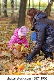 Mum with a daughter walk in autumn park