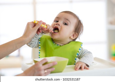Mum feeds baby boy from a spoon with fruit puree