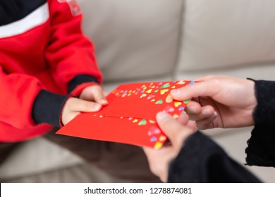 mum giving a red pocket to her son