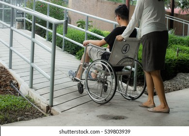 Mum helping her son sitting on wheelchair up the ramp in the park with sunset in background, warm filter