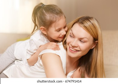 Mum and her cute daughter child girl are playing, smiling and hugging. Happy mother's day. Family holiday and togetherness.