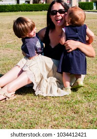 Mum with her two young children is sitting in a meadow and the children are around him hugging her